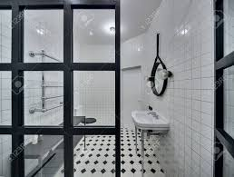 moderne badezimmer mit wänden aus weißen fliesen es gibt weiße waschbecken schwarzen spiegel len glastrennwand weiß schwarz toilette