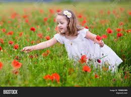 adorable girl in white dress playing in poppy flower field