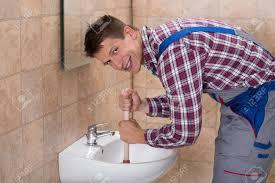 lächelnde junge männliche klempner mit plunger in verstopften waschbecken im badezimmer