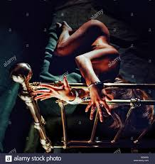 A woman handcuffed to a brass bed frame Stock Royalty