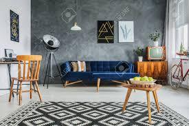 komplett eingerichtetes stilvolles wohnzimmer mit plakaten über blauer mit kissen