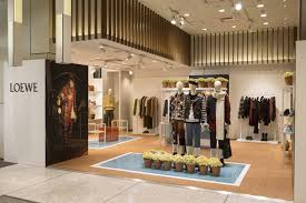 The Pop Up Store Is Funished With Sleek Tiered Displays Clothing Racks And Furnishing A Pristine White Hue Paired Neatly Arranged Potted Plants