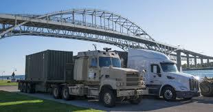100 Blue Trucks Drive Themselves Across Water Bridge