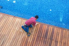 A Man Painting Exterior Wooden Pool Deck Top View