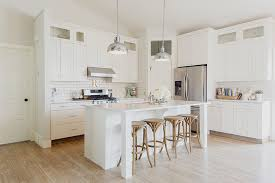 L Shaped Kitchen Features Creamy White Shaker Cabinets Paired With Quartz Countertops And Subway Tiled Backsplash Framing Stainless Steel Hood Over