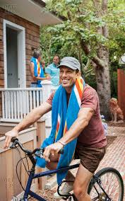 Happy Man Riding Bicycle With Friends In Background