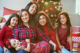 Hispanic Women And Girls Posing Near Christmas Tree