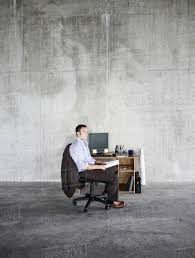 Business Man Sitting At A Small Desk In A Large Empty Raw Office ... Office Chairs Redating Chair Back Bar Stool Wearable Easy To Exquisite For Big Men Your Residence Decor Next Day Chester Leather Large Wing Officechair Eames Lounge Vitra Black Mhattan Home Design Aeron Herman Miller Ergonomic Computer Desk More Best Buy Canada Heavy People Choosing Chairs For Big And Tall Employees Fniture News A Man Seated In A Large Office Chair Leaning Back Checking His Ottoman 10 Neck Pain Think Classic Swopper Motion Seating Swoppercom