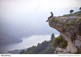 Young Man Sitting On Edge Of Cliff And Looking At River