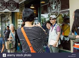 Visitors Take Pictures In Front Of Original Logo Printed Window Starbucks Coffee Flagship Store At Pike Place Market Seattle USA