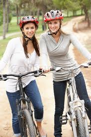 Two Female Friends Riding Bikes In Park