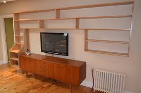 wooden wall mounted shelving unit over mid century modern tv stand