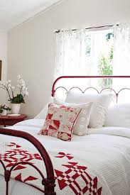 White Bedroom With Red Metal Bed Frame And Quilt At The Foot Of