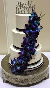 3 Tier buttercream wedding cake decorated with plum and diamond bling ribbons and fresh cascading orchids