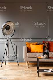 sofa mit bunten kissen in echtes foto grauen wohnzimmer interieur mit studio le stehend formteil auf wand und metall tisch mit dekor stockfoto