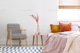 blumen auf dem tisch zwischen gemusterten sessel und rosa bett im schlafzimmer innenraum mit fenster echtes foto stockfoto und mehr bilder