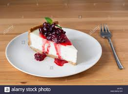 Cheesecake slice with sweet cherry sauce and mint leaf on white plate on wooden table