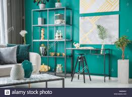 schwarzer stuhl am schreibtisch gegen grüne wand mit gold