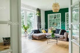 stilvolle einrichtung mit sofa farben kissen blumen und holzboden sonnige und helle wohnzimmer mit großen fenster und design kommode stockfoto und