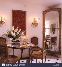 Tall Antique Mirror In Corner Of Townhouse Dining Room With Table And Cane Back Chairs