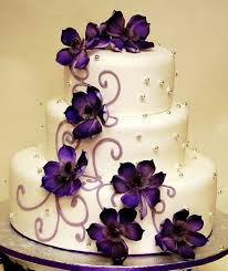 Wedding cake white with silver beads and purple flowers garnishing this elegant and beautiful cake