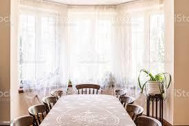 alten stil esszimmer eingerichtet mit einem großen fenster mit vorhängen tisch mit stühlen und pflanze dekoriert echtes foto stockfoto und mehr bilder
