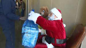 Santa Claus passes out ts at Open Door Mission