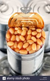 TIN FOOD CANS STACKED WITH ONE CAN OPEN FILLED BAKED BEANS IN TOMATO SAUCE