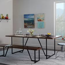 Geometry Angled Iron Legs Provide The Sturdy Base For Geometric Dining Table Made From Solid Acacia Wood In A Rich Dark Walnut Finish