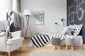gemütliches schlafzimmer mit tafelwand kleiderständer und sessel