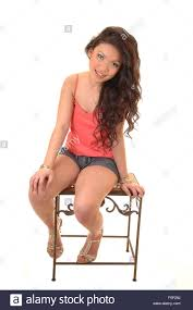 a young beautiful asian woman sitting in shorts and a pink blouse