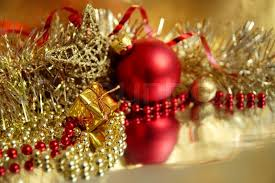 Still Life Of Red And Gold Christmas Ornaments In The Foreground A Small Gift