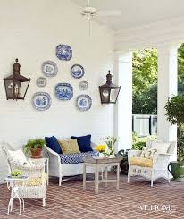 Porch With Wall Lanterns Blue And White Transferware Plates Wicker Furnishings Add Some Extra Pillows