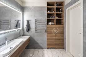 zeitgenössisches badezimmer mit grauen und weißen fliesen es gibt großen spiegel mit leuchtenden len tischplatte mit holzschubladen und
