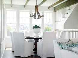 Beach Style Dining Room With Round Table And White Slipcovered Chairs