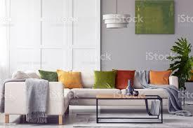 grünen kissen und graue decke auf ecksofa im wohnzimmer interieur mit le über dem tisch echtes foto stockfoto und mehr bilder beton