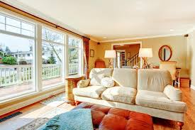 Download Floor To Ceiling Windows Living Room With A Rustic Beige Couch Stock Image