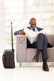 Une Femme Afro Américaine En Lisant Le Journal Homme D Affaires Noir Avec Ordinateur Tablette à L Aéroport Banque D