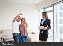 Getting Keys After Buying Apartment Couple And Real Estate Agen Stock Photo