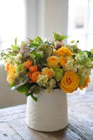 Warm yellow and green arrangement roses stocks hellebores spray