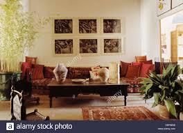 gruppe bildern über lange sofa mit roten kissen im