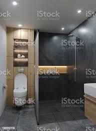 moderne minimalistische neues bad mit zement beton grunge materialien mit holz und led warm leuchten mit strahlern an decke wand wc konzept
