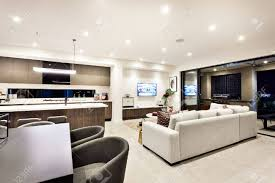 moderne wohnzimmer mit fernseher und sofas und kissen neben einem essbereich und küche gibt es einen eingang zu einer außenterrasse