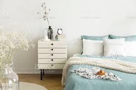 ein helles schlafzimmer interieur mit salbei grünweiße bettwäsche kissen auf bett und ein nachttisch schublade echtes foto stockfoto und mehr bilder