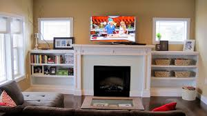 black fireplace plus shelf and tv above on the middle of white