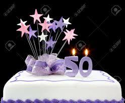 torte mit der zahl 50 kerzen dekoriert mit bändern und formen in pastell tönen auf schwarzem hintergrund