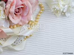Silk Roses In A Pink Blush Color Arranged With Vintage Lace Pearls And Ivory Colored Satin Ribbon On Textured Fabric Background