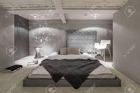 grau weißes schlafzimmer mit bodenbett und ziegeldecke
