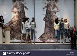 A Woman Standing At The Side Of Fashion Shop Window Display