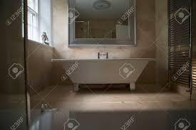 einem gestalteten badezimmer ein großer stand alone badewanne steht in der mitte des bildes mit einem großen spiegel darüber das